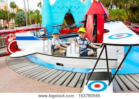 Two little funny kid boys riding on roundabout carousel in amusement park. Happy children, friends having fun outdoors on sunny day