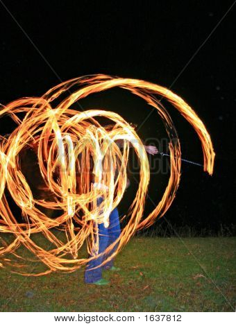 A fire dancer with fire trails creating beautiful effect poster