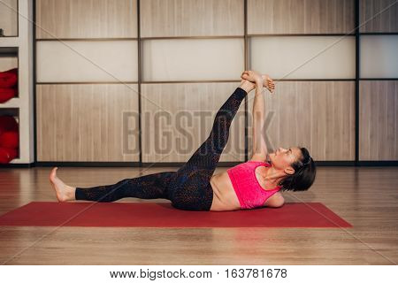 Woman doing Reclining Big Toe yoga pose, this pose stretches groins, thighs, hamstrings, calves, relieves backache