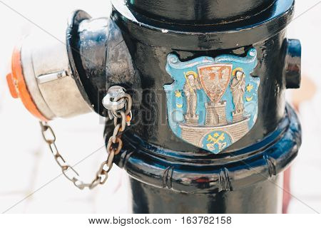 Old fire hydrant with the coat of arms of Poznań; Poland - shallow depth of field