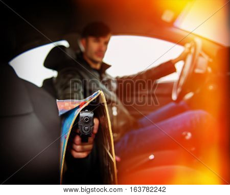 criminal man with a gun sitting in the car and threatens