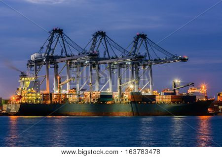 Containers loading by crane in the twilight Trade Port Shipping