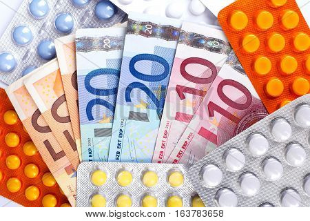 Photo of a Euro money bills and colorful pills