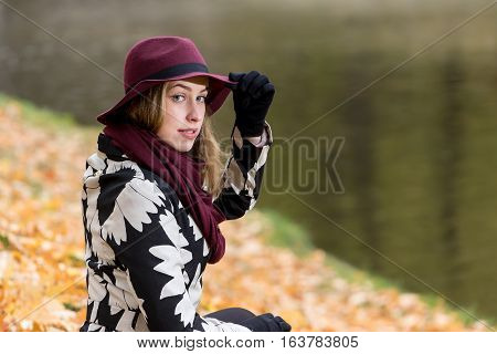 Woman in a floral patterned coat and wine red hat in the park by the river. Happy girl and colorful autumn forest. Portrait of a lady yellow green red and brown leaves background