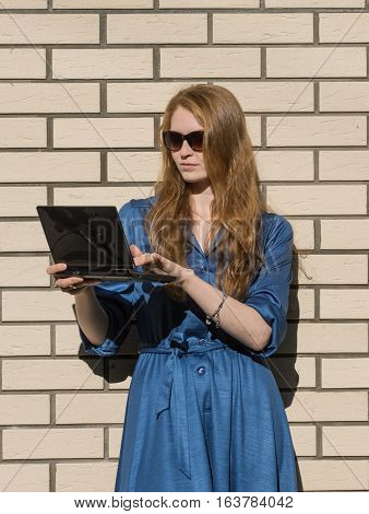 Woman in casual wear leans against white brick wall. Red hair girl is standing outside an office holding a tablet and house background. Lady doing the computer work. Outdoors lifestyle.
