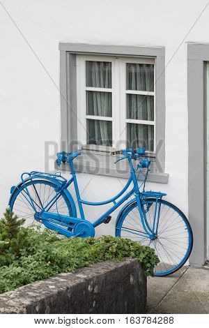The decoration of vintage bicycle and white building with green door. Old blue retro bike and holiday house background.