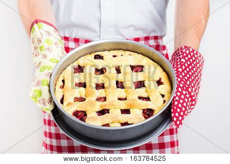Man baked pie, chef holding baked pie, freshly baked pie, fresh fruit dessert