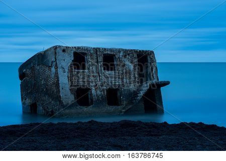 Liepaja beach bunker. Brick house soft water waves and rocks. Abandoned military ruins facilities in a stormy sea. Barracks building in the Baltic sea. Liepaja Latvia Europe.