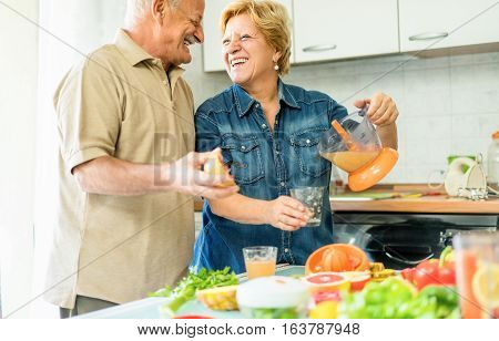 Happy senior couple preparing healthy vegetarian breakfast with fruits and vegetables - Old cheerful people taking care about nutrition - Healthvegan and bio concept - Focus on woman - Warm filter