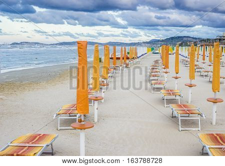 Rows Of Closed Umbrellas And Deckchairs On The Empty Beach