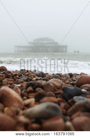 View of Brighton pebble beach, with the old abandoned West Pier in the background, in a misty rainy day.