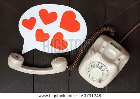 talking on the phone concept as a set of hearts flying out of the tube / greetings on the day of lovers