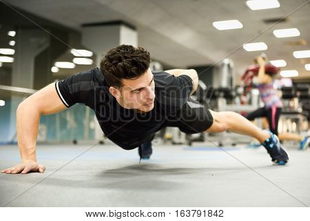 Attractive Man Doin Pushups In The Gym