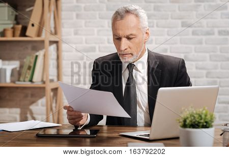 Good results. Good looking concentrated senior executive working at his office at his desk and looking through some important data while holding a sheet of paper