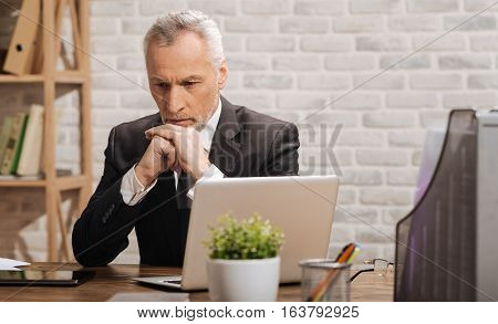 Concerning issues. Handsome worried senior businessman figuring ways out of complicated situation while sitting at his desk in an office
