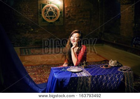 young pretty asian girl in bright colored interior on carpet view fairy