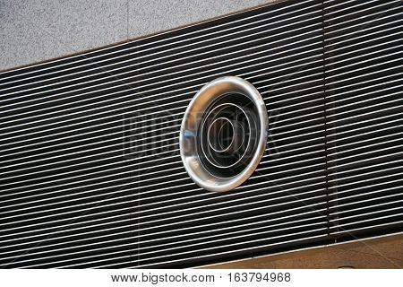 Closeup of round shape ventilation system hole on a wall in a large building