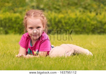 A little girl playing with a cuddly toy on the grass in a park