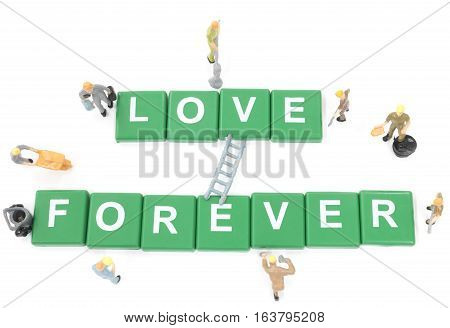 Miniature worker team building word love forever on white background