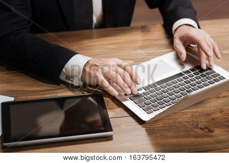 Message of utmost importance. Handsome focused senior executive writing an email using his computer while sitting at his table in an office