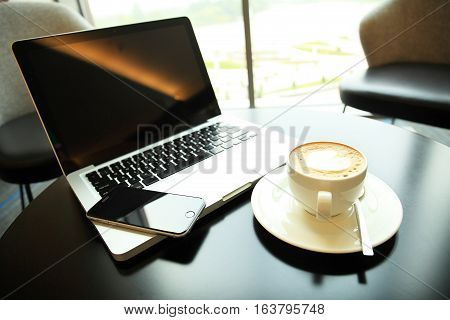 computer laptop and coffee in coffee shop vintage color tone