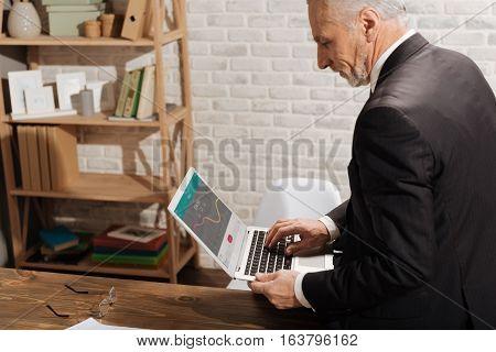 Power of visual representation. Experienced attractive mature gentleman looking at the screen of his laptop and reading data on sales while sitting on his desk in the office