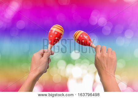 Hand holds maracas on abstract blurry bokeh background