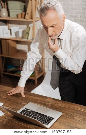 How can I fix it. Emotional distressed serious businessman perusing a contract using his laptop while standing at the table and nervously touching his chin