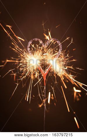 Burning sparkler in heart shape against black background