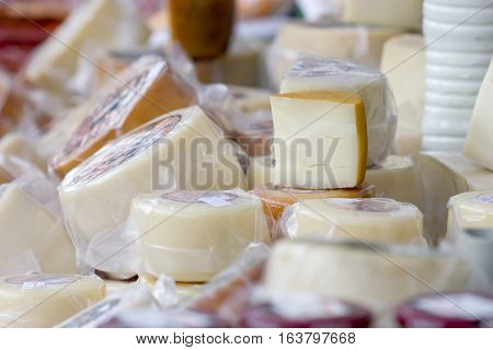 Background image of a selection of different goat and sheep cheeses with a big cheese wedge above all of them.