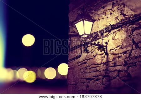 City lights and lamppost in the facade.Stone wall background at night.night scenery