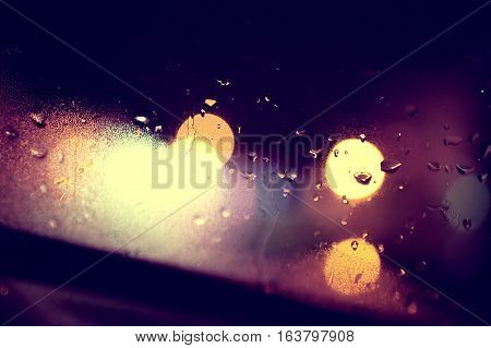 Wet window background and city lights.Rainny night through the glass