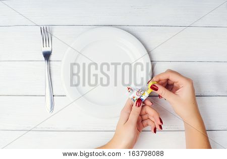 Concept photo: food from a tube. Not healthy, genetically modified food. Woman's hands push from the tube on a white plate at white wooden background. Preparing to eat food from the tube.