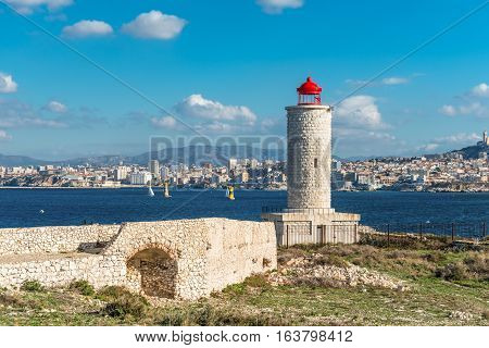 View on the Chateau d'If Lighthouse on Castle IF fortress-island with Marseille in the background Provence France. The chateau was made famous by the Alexandre Dumas novel The Count of Monte Cristo.