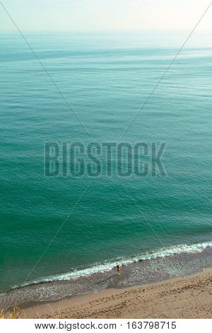 View of the open Mediterranean sea and it's magnitude compared to the size of a person entering the water by the beach shore.