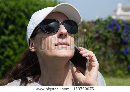 portrait of brunette woman with white cap black sunglasses and grey shirt listen to mobile phone smartphone with green plants garden background