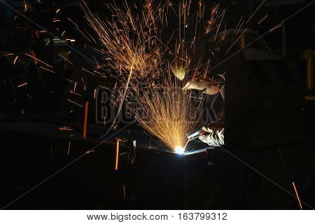 Welder arc Gouging carbon electrode rods with sparks and smoke in manufacturing