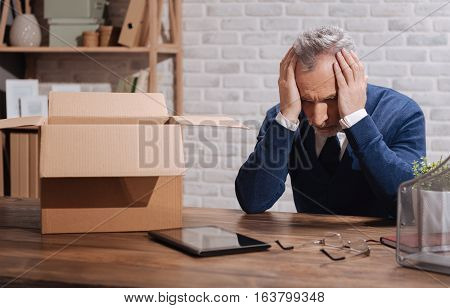 So much trouble. Upset distressed senior gentleman thinking about the end of his career while holding his head in his hands and sitting at the office table with things packed away