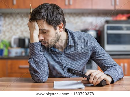 Depressed Man Is Writing Letter And Holds Pistol In Hand. Suicid