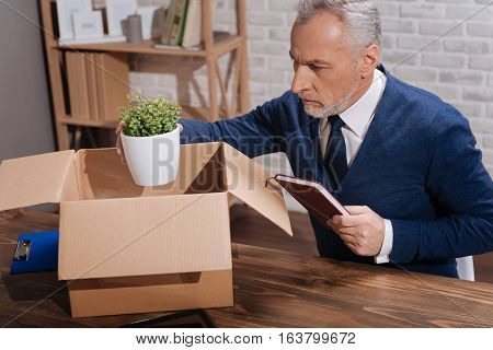 My favorite part of the office. Concerned depressed mature gentleman holding his plant above a box during packing his stuff after his dismissal
