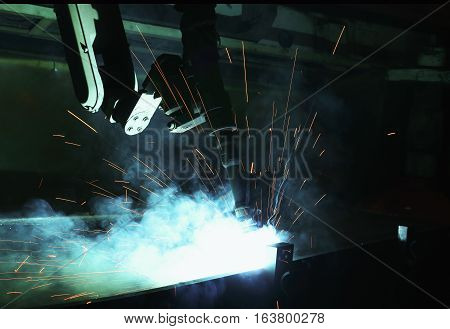 Robots used Metal Welding with sparks and smoke in manufacturing