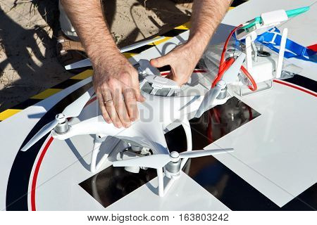 Quadrocopter preparing to fly. Man's hand lies on drone