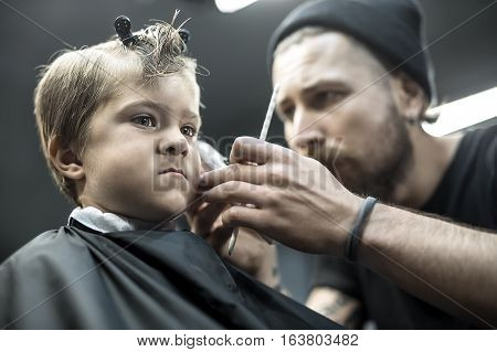 Amazing little boy in the black salon cape in the barbershop. Bearded barber in the black cap makes a hairstyle with a trimmer and a comb. Low aperture closeup photo. Horizontal.