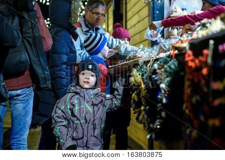 Kiev Ukraine 21.12.2016 Cute Little Kid Boy On German Christmas Market. Happy Child In Winter Clothe