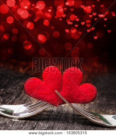 Two red hearts are stuck in two forks with red hearts in the background