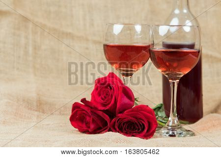 Two glasses of wine with three roses laying on burlap