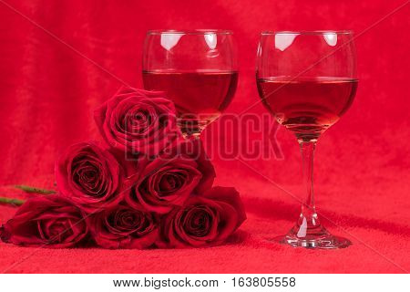 Two glasses of wine next to a bouquet of roses