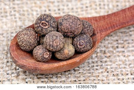 Allspice in a wooden spoon on table