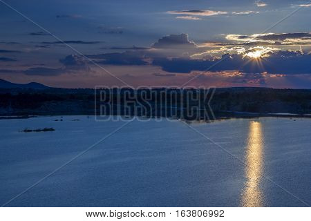 Sunset over the lake or the sea. The sun shines through the clouds reflected in water