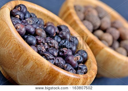 Juniper and allspice in a bowls on slate